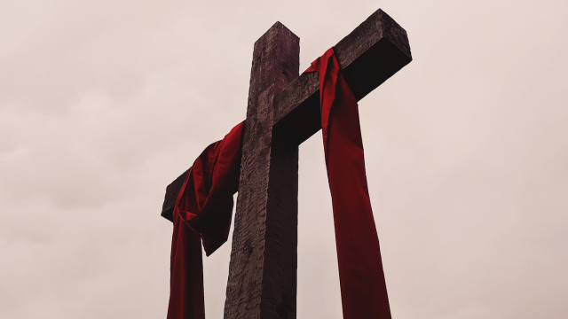 cross draped with red cloth