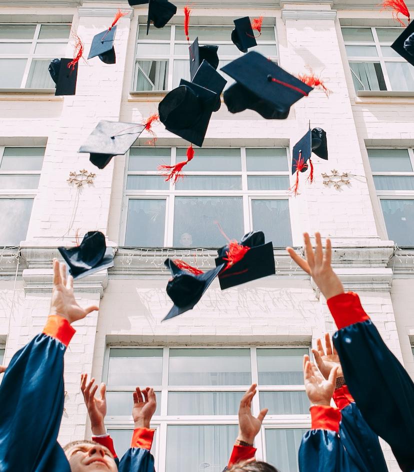 college graduates tossing their caps