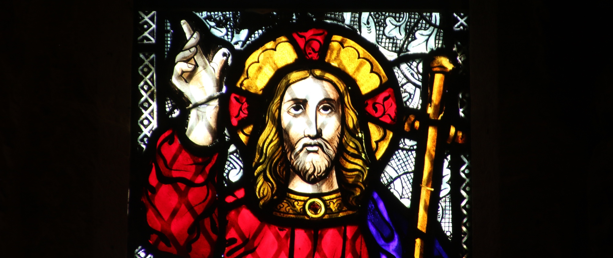 jesus pointing toward the sky on stained glass window