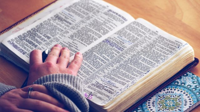 open bible with highlights and a hand resting on it