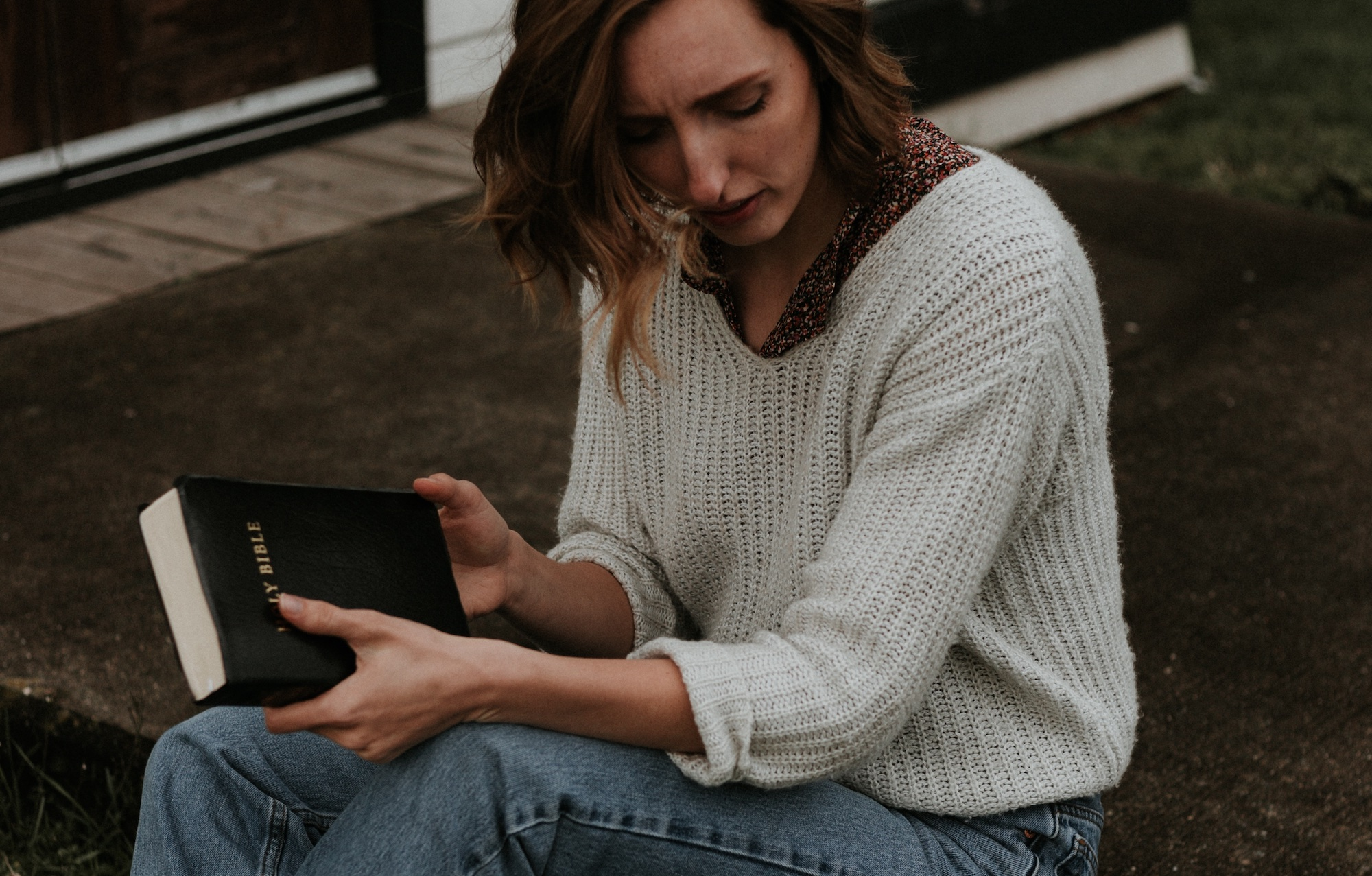 woman sitting with bible in sweater