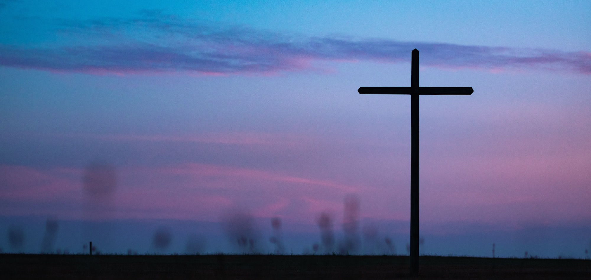 cross on a blue and purple sunset