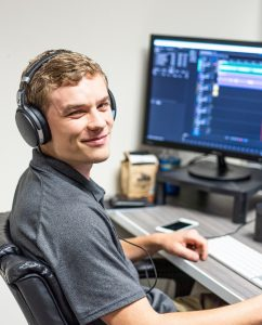 Nate Mulder sitting at his desk while editing a podcast episode