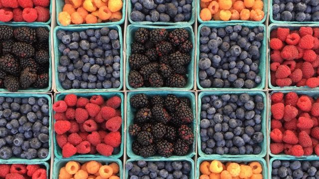 assortment of berries in green containers
