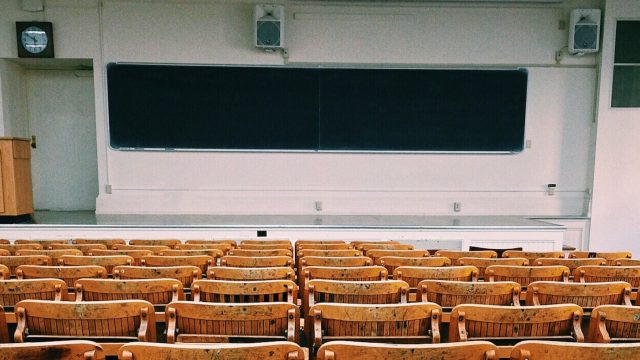 an empty lecture style classroom with a black chalkboard at the front