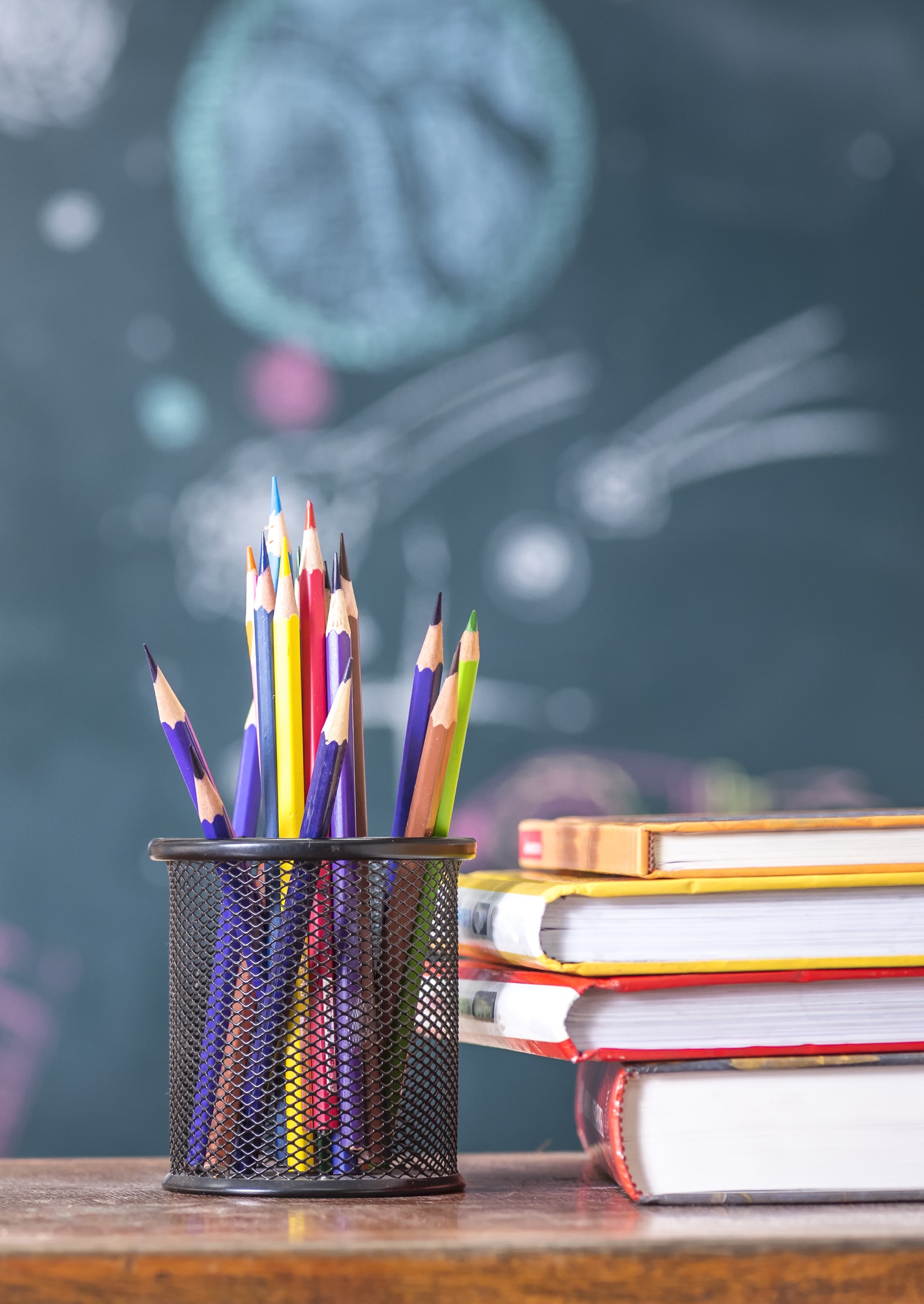 a mesh metal cup of colored pencils sitting next to a stack of school books, with a background of a chalkboard with space images on it