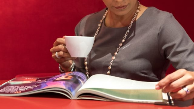 woman holding a cup and looking at a magazine