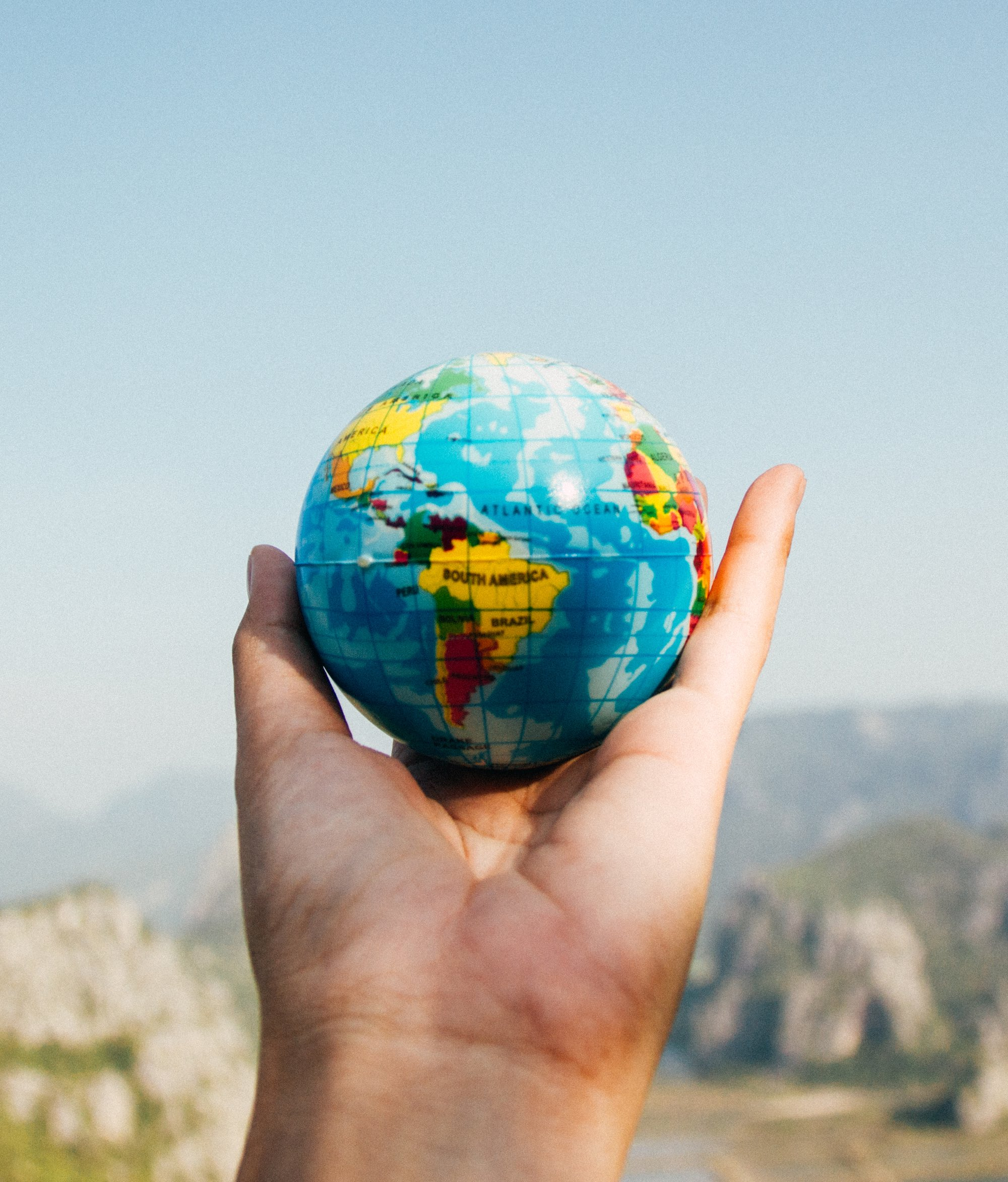 a hand holding a small globe