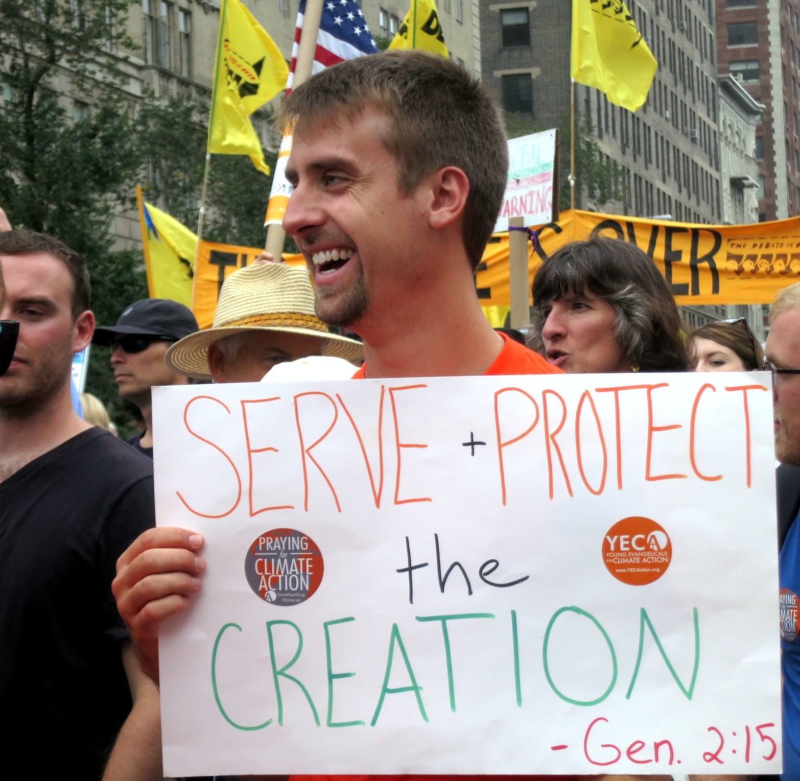 """Man holding sign reading """"serve and protect the creation, Gen. 2:15"""""""