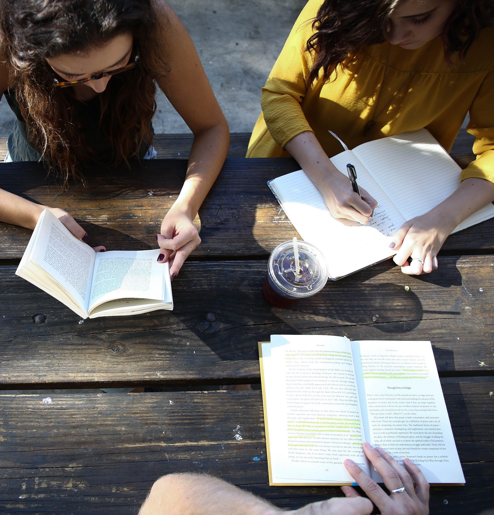 three people reading open books at a table