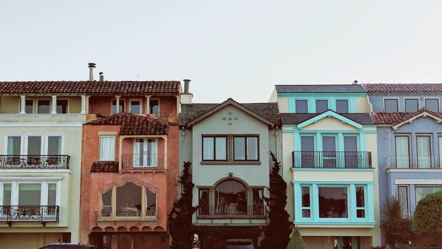 many colored houses in a row on a street