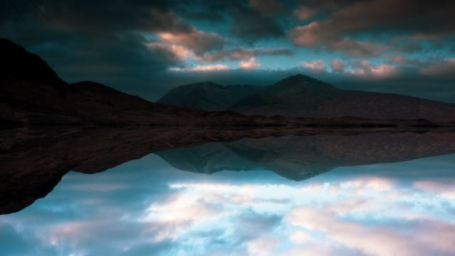 reflection of sky on lake with mountains behind