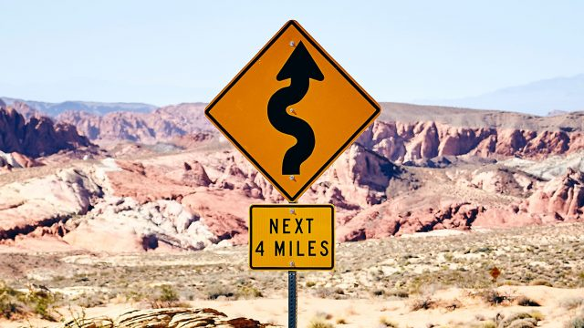 curvy road sign in front of canyon landscape