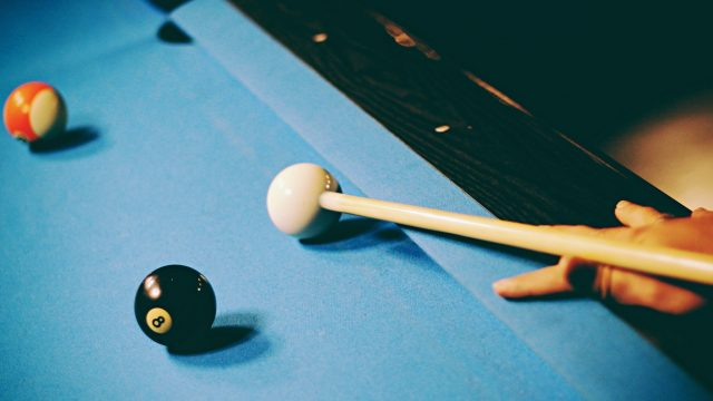 a hand shooting a cue ball on a billiards table