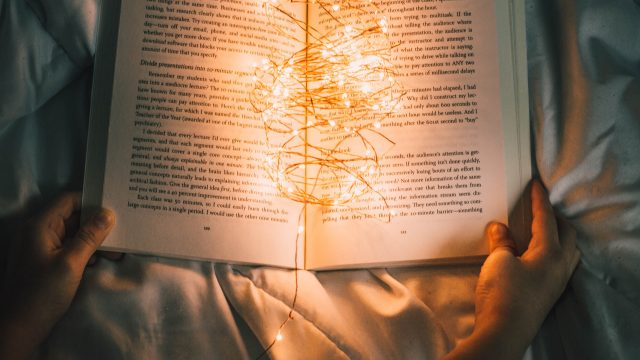 book on bed with string of lights