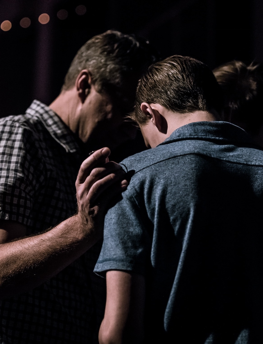 two men huddled together praying
