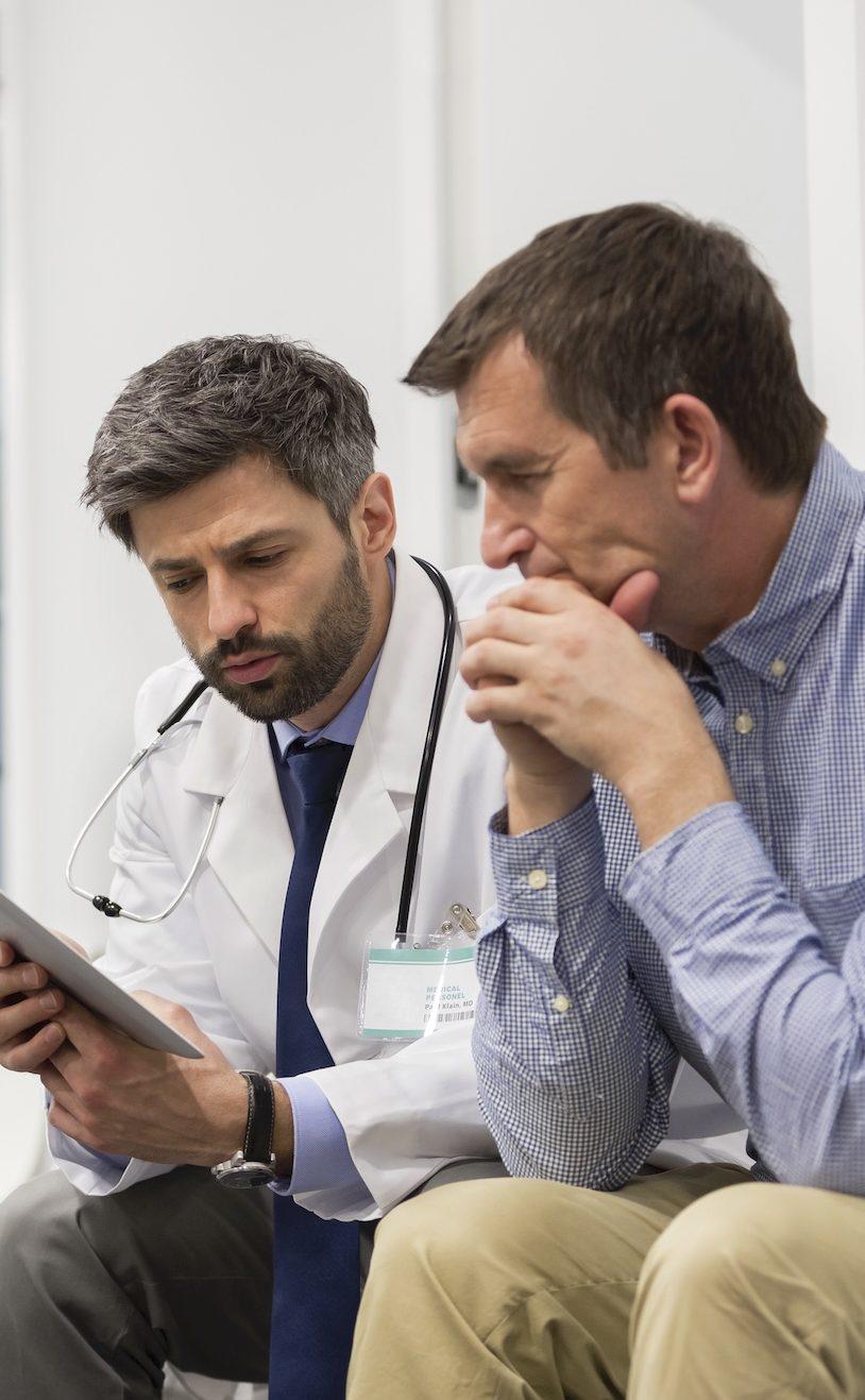 man and his doctor looking at iPad