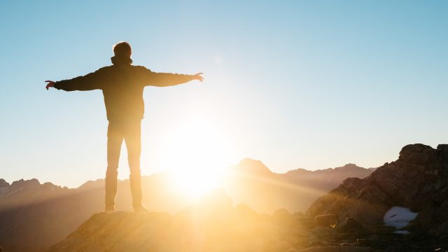 man standing on a mountain and the sun is rising