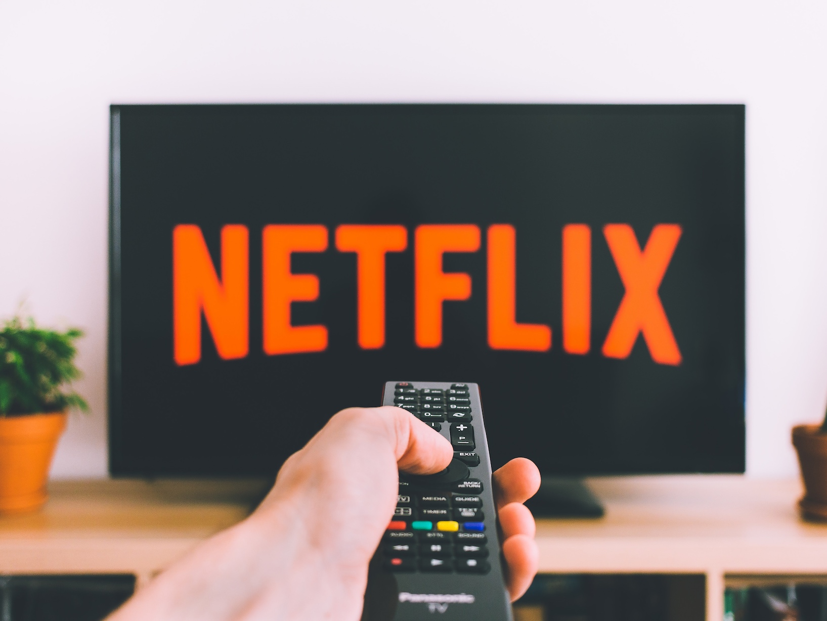 Netflix logo on a TV with a hand and a remote in the foreground