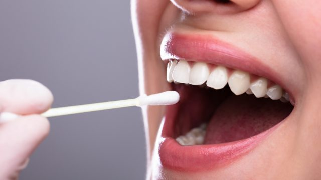 a mouth with a cotton swab entering it