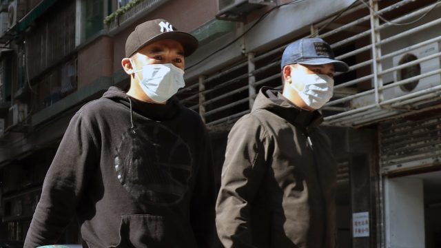 2 men in surgical masks walking in the street