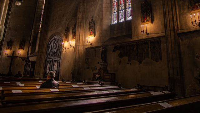 man sitting alone in an empty church