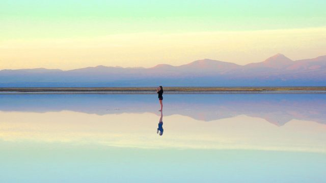 woman standing near a body of water reflection