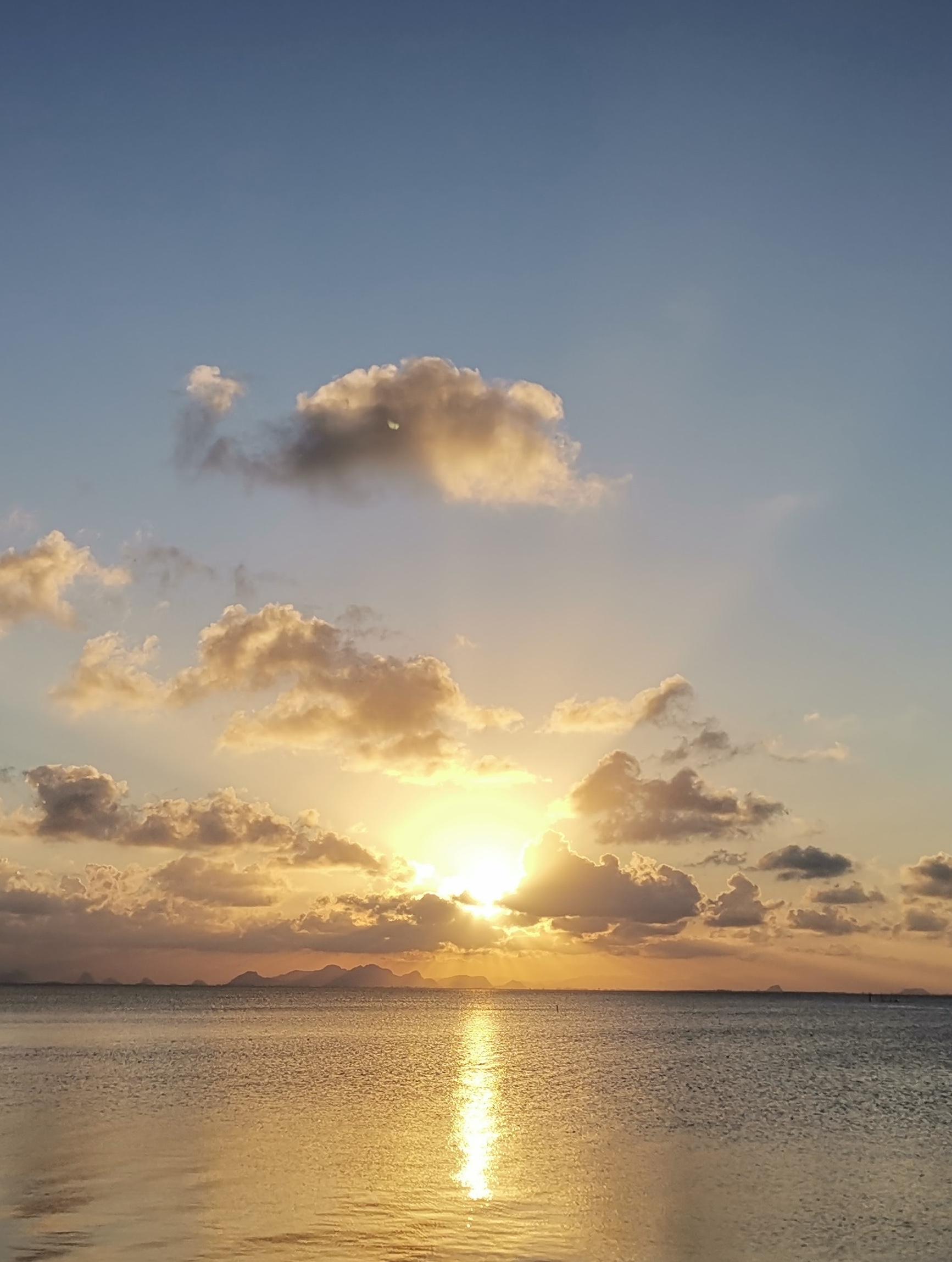 sun peeking through clouds over the ocean