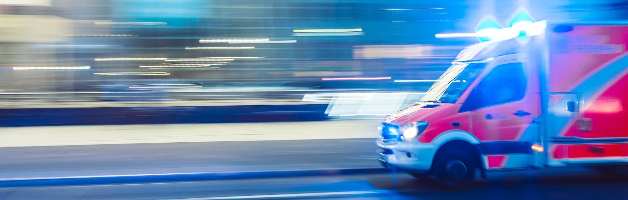 flashing ambulance drives fast on road