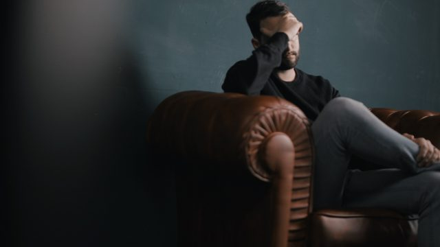 man covering face and sitting on a couch