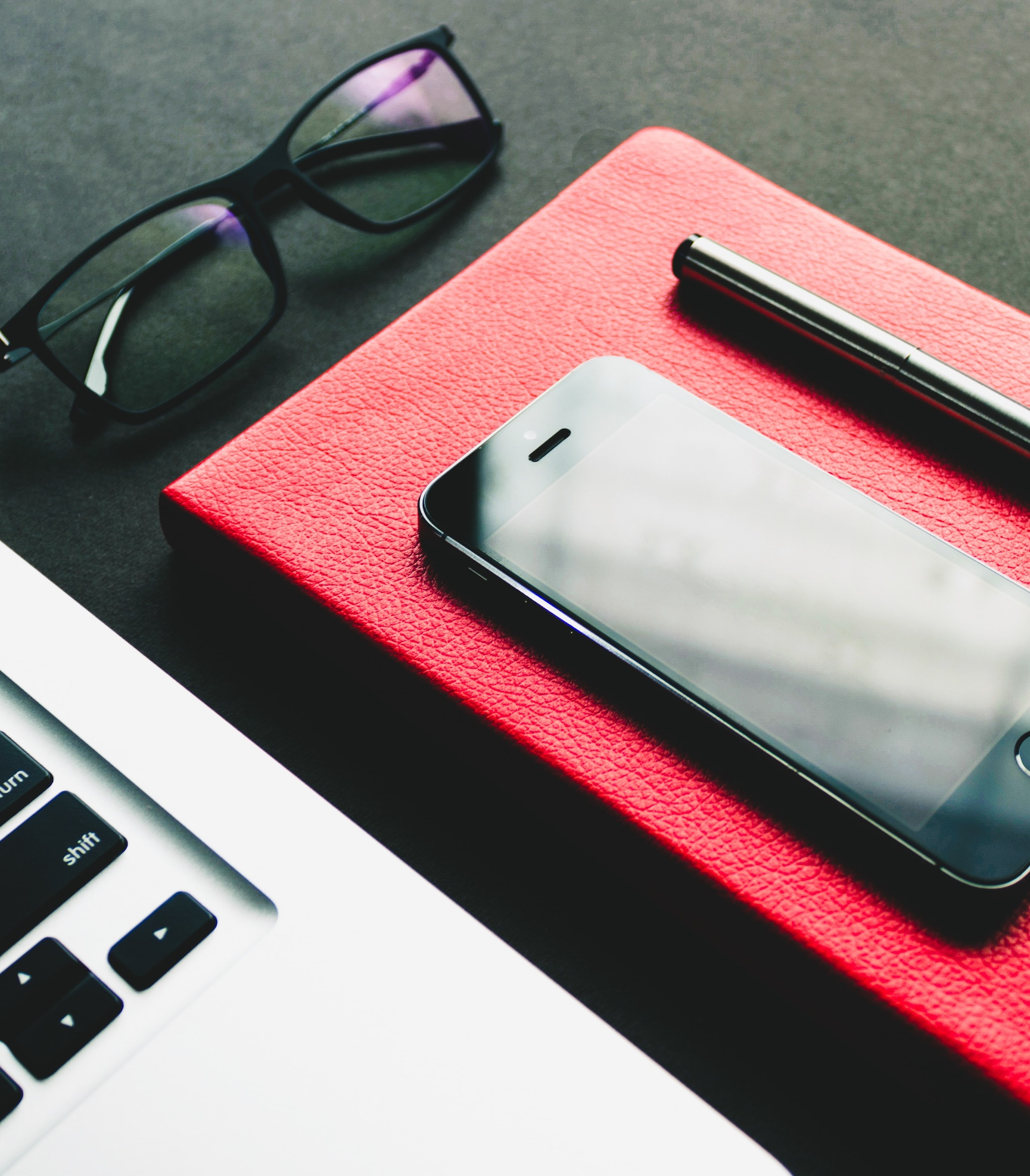 phone and pen on top of notebook, sitting next to an open laptop and glasses