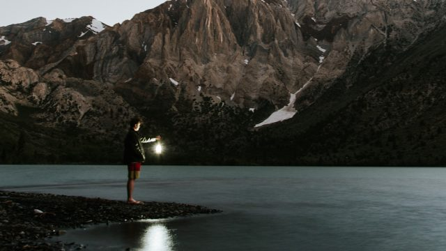 man holding lantern by a lake