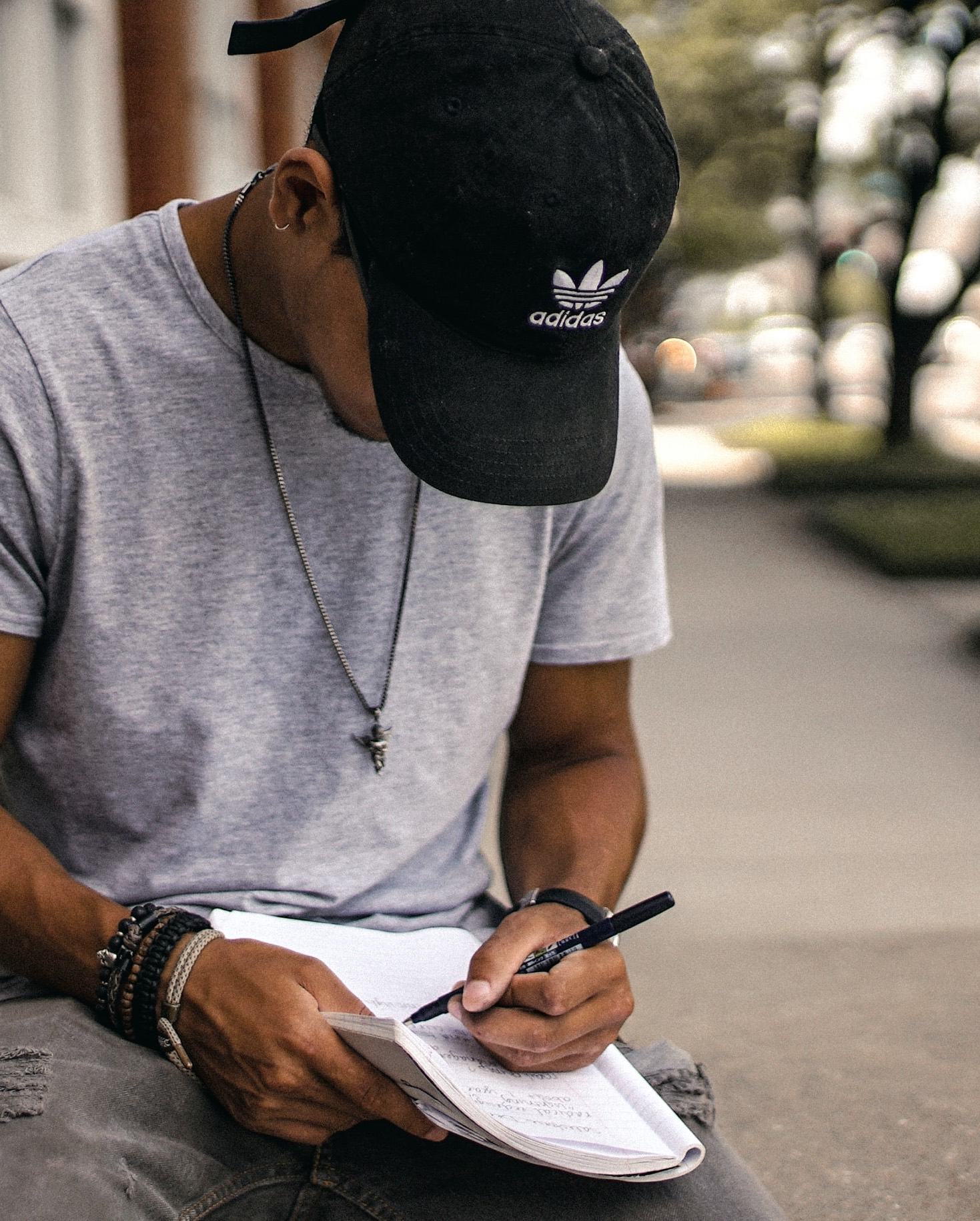 man in a baseball hat writing in a notebook