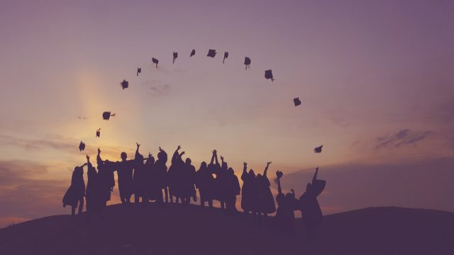 a group of graduates outside throwing their caps up in the air into an arch