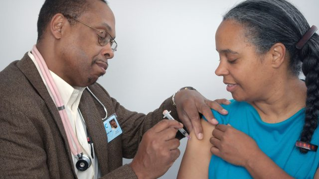 a man administers a vaccine into a woman's arm