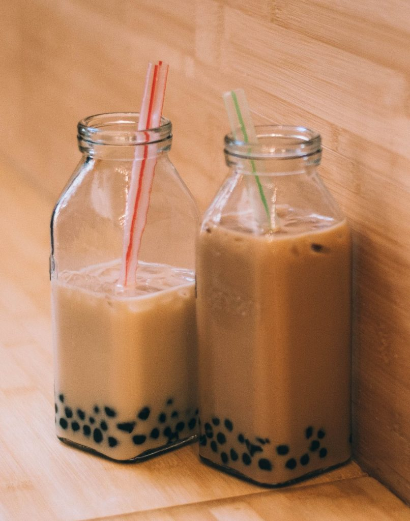 bubble tea in two glass bottles with big straws