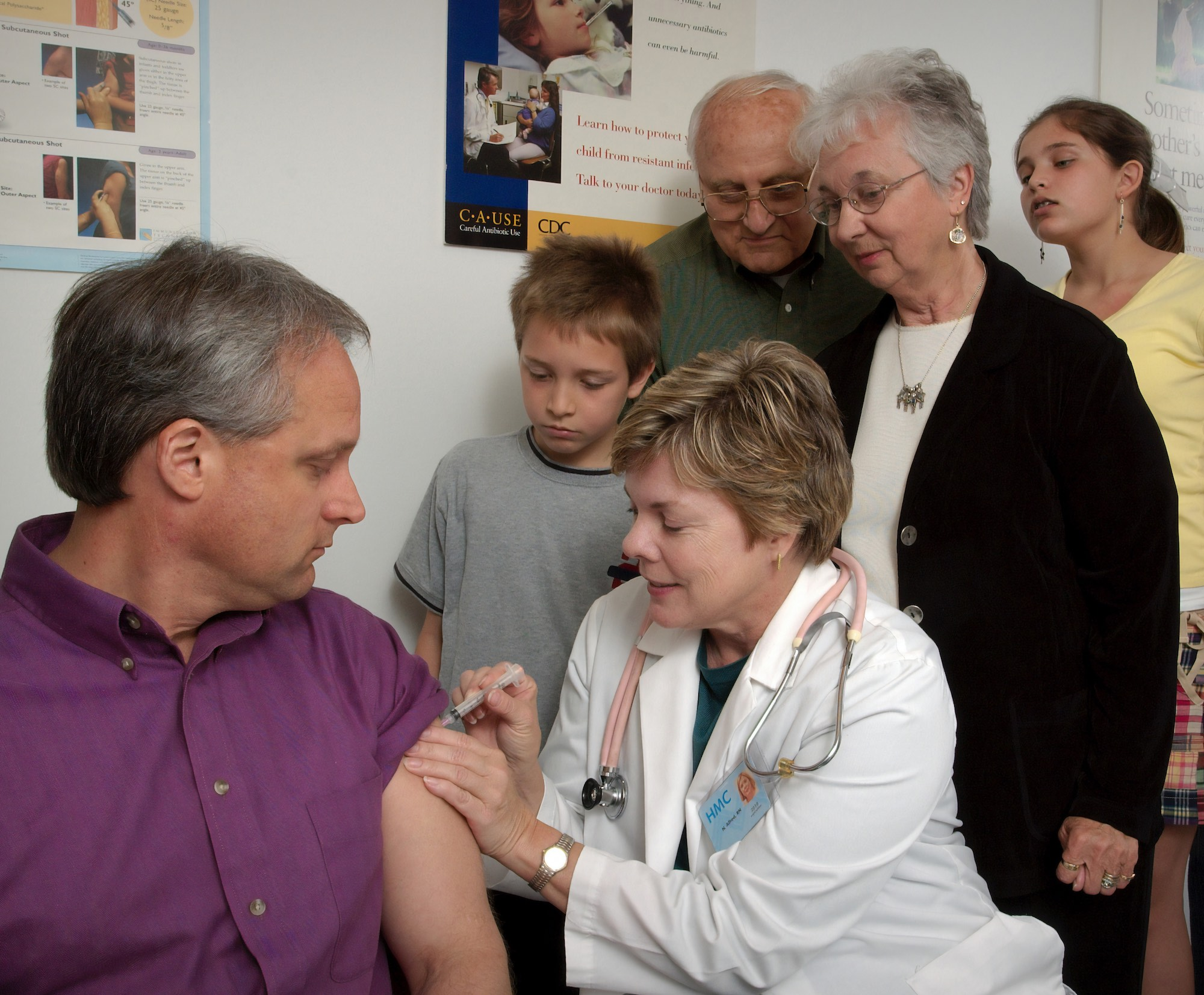 a woman giving a vaccine to a man while 4 other people look on
