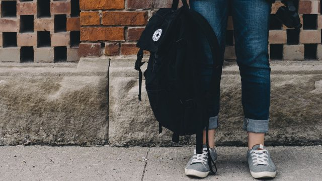 a person's legs standing on a sidewalk, holding a backpack