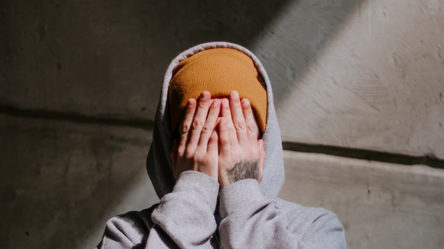 person in yellow beanie and gray hoodie covering face with hands