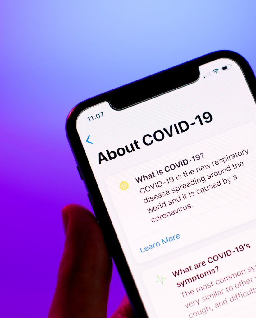 "iphone with ""About COVID-19"" information displaying on the screen"