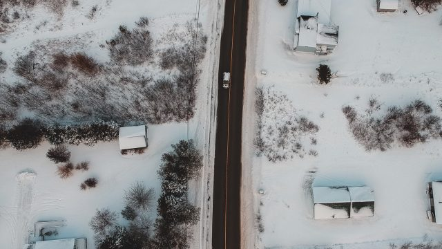 a car driving in a snowy neighborhood