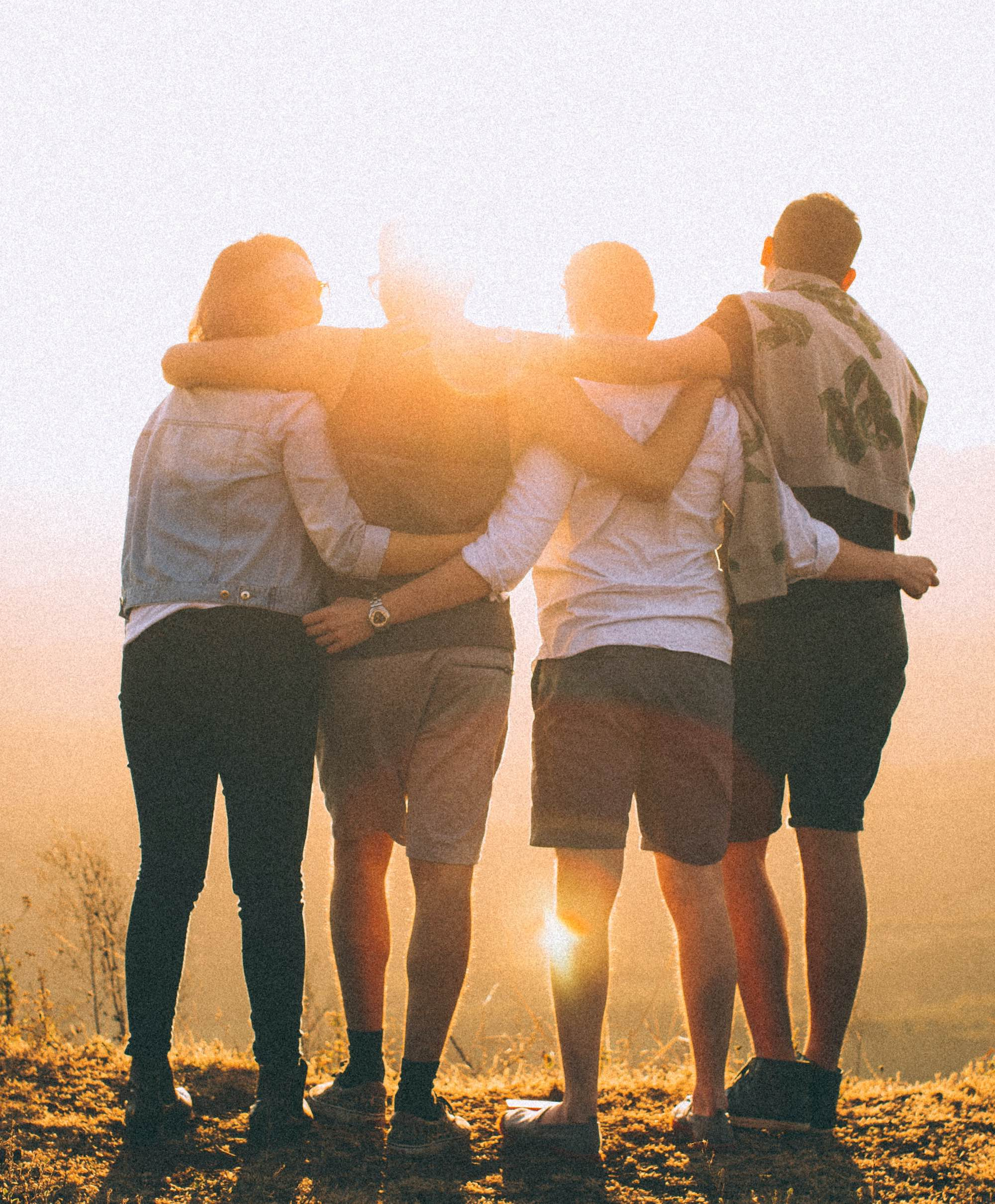 group of friends facing the sun with their arms around each other's backs
