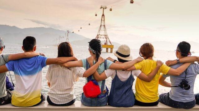 eight people sitting on a pier with their arms around each other's shoulders