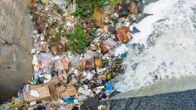 trash piling up next to a water dam