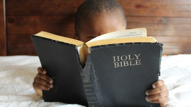 young boy reading a bible