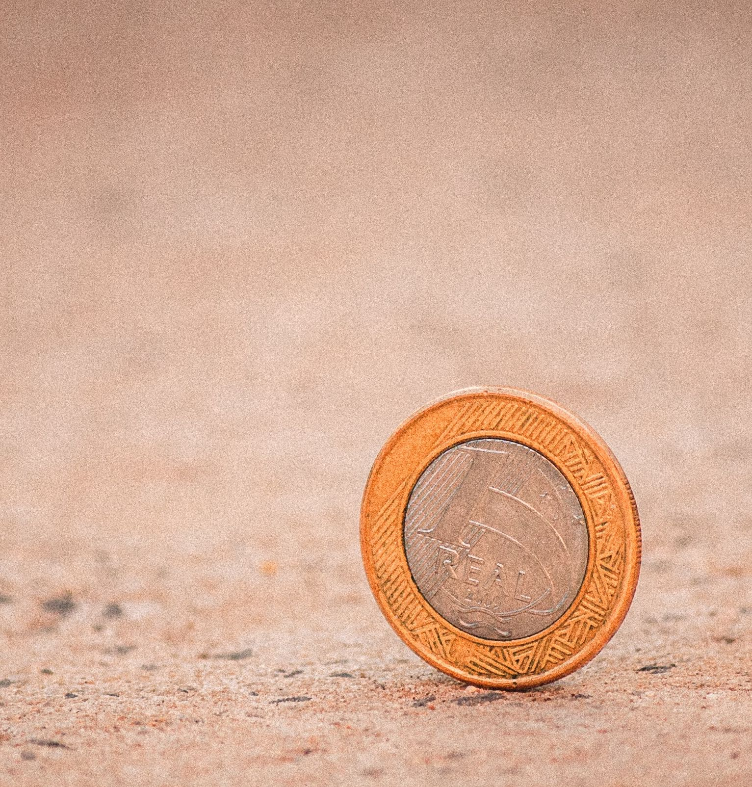 coin standing upright on pavement