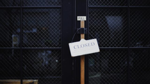 a sign saying CLOSED hanging over a door handle