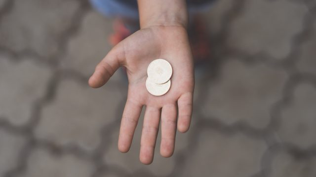 hand holding two coins