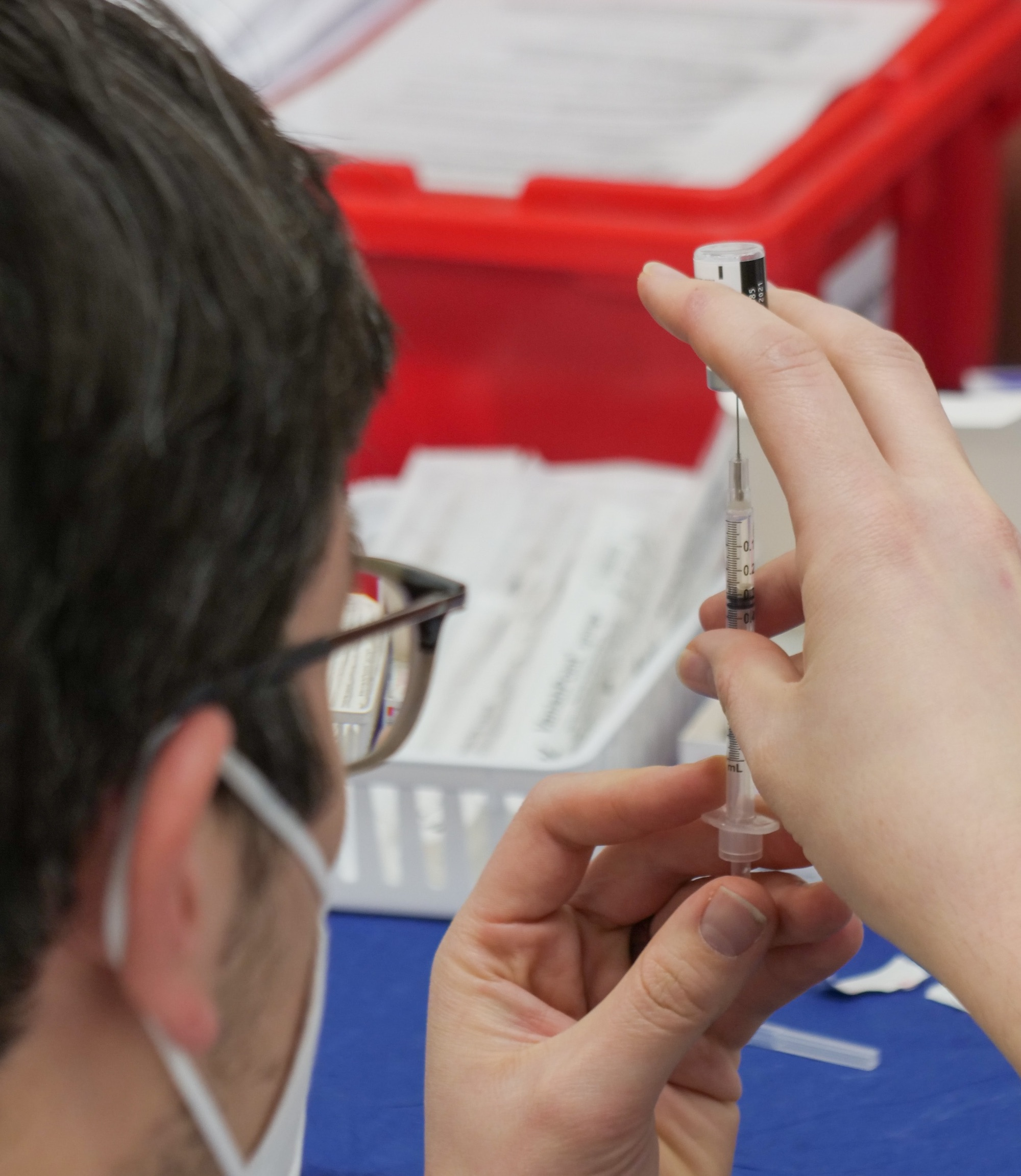 a masked individual withdraws a vaccine from a vial