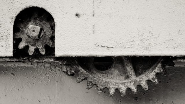 two gears, partly covered by a panel